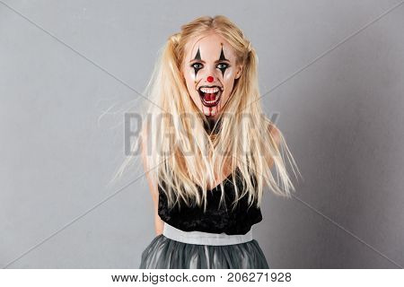 Frightening screaming blonde woman in halloween make up looking at the camera over gray background