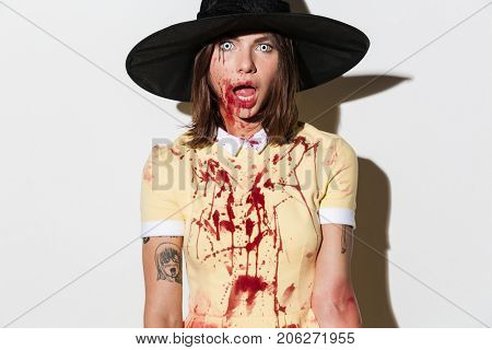 Close up image of frightening woman in halloween costume looking at the camera with open mouth over white background