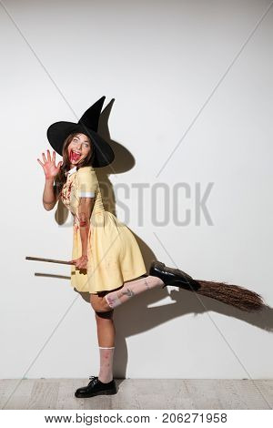 Full length image of happy woman in halloween costume with open mouth flying on broom like witch and looking at the camera over white background