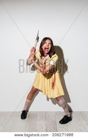 Full length image of mad zombie woman in dress ready to attack with an axe over white background