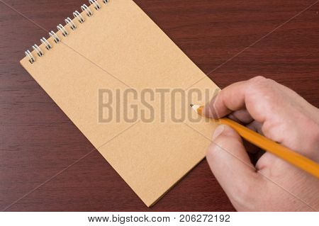 A hand writing in notebook. Closeup of pencil writing to a blank notebook. In Search Of Inspiration. A man with an empty notebook. Blank paper waiting for idea with hand and pencil . hands writing
