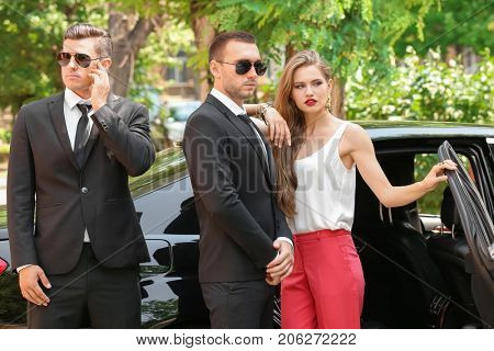 Young businesswoman with bodyguards near car outdoors