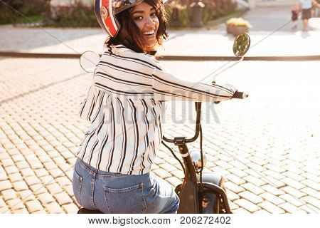 Back view of joyful african woman in moto helmet rides on modern motorbike outdoors and looking at the camera