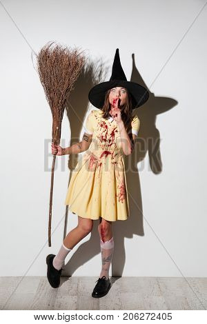 Full length image of young woman in halloween costume posing with broom and looking at the camera while showing silence gesture over white background