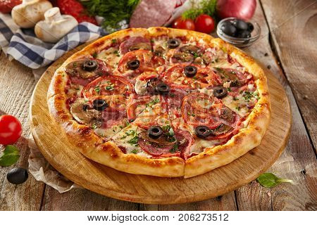 Pizza Restaurant Menu - Delicious Fresh Pizza with Sausages, Tomatoes and Mushrooms.Pizza on Rustic Wooden Table with Ingredients