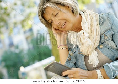 Senior woman reading message on smartphone, citylife