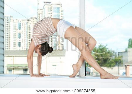 Young beautiful woman doing yoga pose against window, indoors