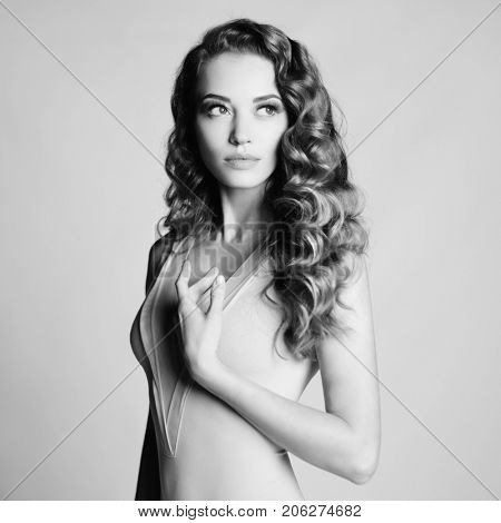 Black and white art portrait of beautiful sensual woman with elegant hairstyle on gray background