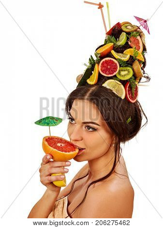 Girl drinking fruit cocktail on summer party. Woman with fresh fruits hairstyle and bare back hold halves of grapefruit with cocktail umbrella. Masks made from natural ingredients for hair.