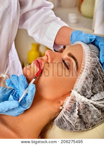 Filler injection for female forehead face. Plastic aesthetic facial surgery in beauty clinic. Doctor in medical gloves with syringe injects lips augmentation.