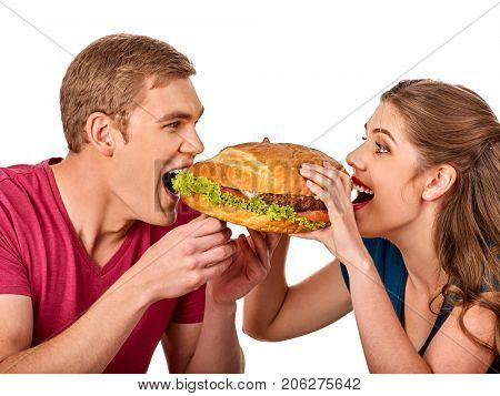 Couple eating fast food. Man and woman treat big hamburger with ham. Friends give burder junk on white background isolated. Enamored people eat huge sandwich. How to feed husband concept.