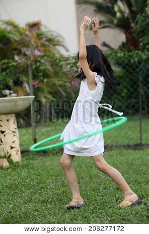 chinese girl playing hula at the garden