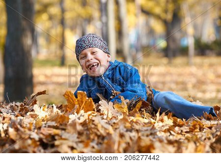 boy lie on yellow leaves in autumn park, bright sunny day, fallen leaves on background
