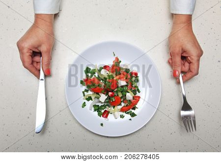 hands with kitchen flatware and fresh vegetables sliced in white plate
