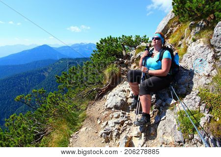 Overweight woman enjoying life. Nordic walking in alpine landscape. Healthy lifestyle and weight loss concept. Karwendel Alps, Bavaria, Germany.