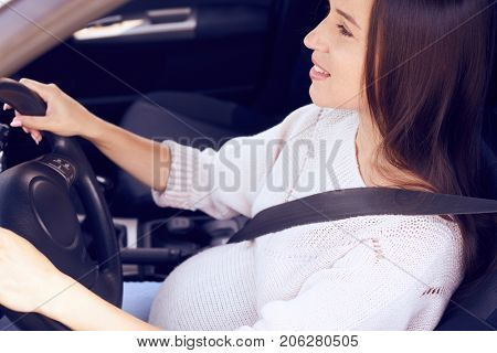 Closeup of happy pregnant female driver steering car with safety belt