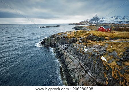 Clif with traditional red rorbu house on Litl-Toppoya islet on Lofoten Islands, Norway in winter