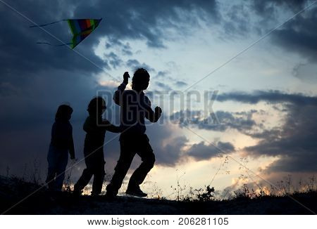 Children playing kite on summer sunset meadow silhouetted.