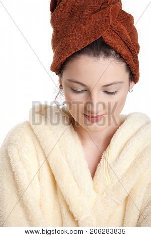 Portrait of young attractive teenager in bathrobe, hair wrapped in towel, looking down, smiling. Isolated on white.