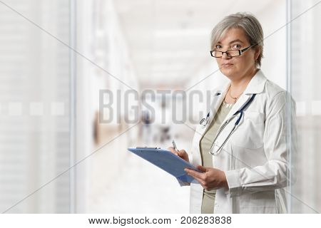 Mature female doctor standing on hospital corridor, looking at clipboard.