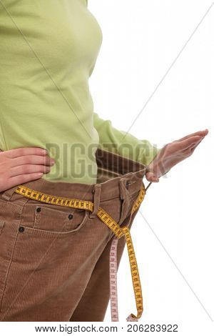 Teenager girl wearing several sizes too big trousers, holding it up with hand, using measuring tape as belt. Cut out, isolated on white.