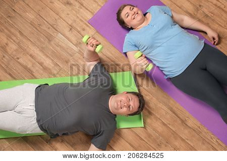 Overweight couple training together on wooden floor