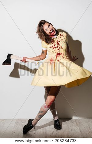 Full length image of mad happy zombie woman moving with an axe and looking at the camera over gray background