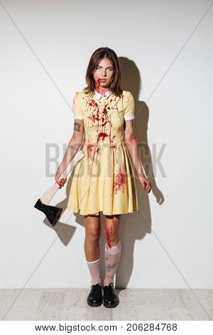 Full length image of mad zombie woman posing with an axe and looking at the camera over white background