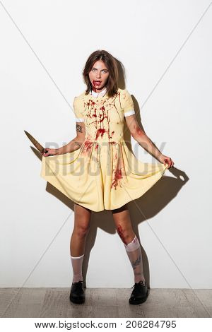Full length image of frightening zombie woman in dress with knife looking at the camera over white background