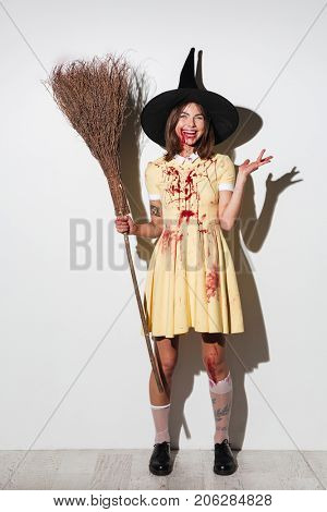 Full length image of laughing woman in halloween costume holding broom and looking at the camera over white background
