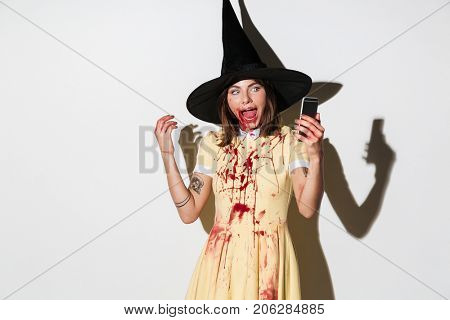 Frightening woman in halloween costume making selfie on smartphone over white background