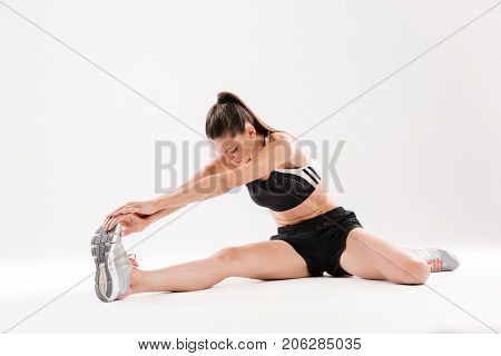 Full length portrait of a healthy motivated sportwoman stretching muscles while sitting on the floor isolated over white background
