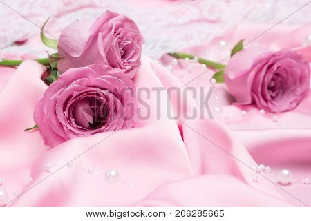 Pink roses on folded silk fabric with white bead strand. Romantic background with flowers