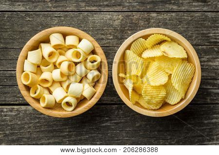 Crispy potato chips and rings in bowl. Salted potato chips. Top view.