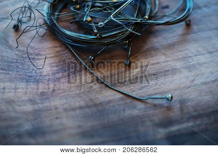 Old guitar strings, on grungy old wooden desk. Ball-end,  coiled and bundled.