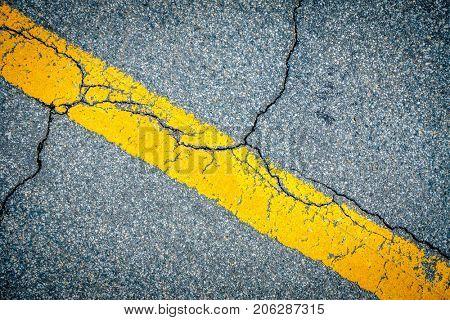 Closeup image of road marking and cracks in asphalt