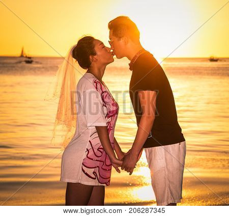 BORACAY, PHILIPHINES-MARCH 17, 2017: Asinan prime adult male groom and female bride holding hands and kissing barefoot on March 17, 2017 at Wite beach. Boacay island , Philiphines.