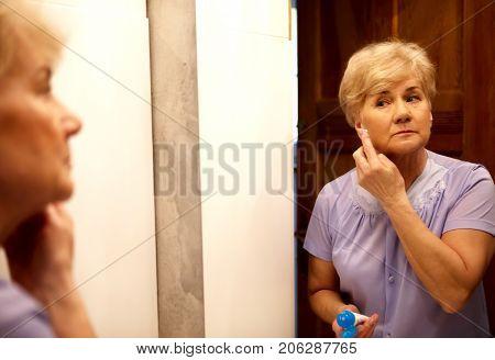Portrait of senior woman applying anti-aging cream on her face.