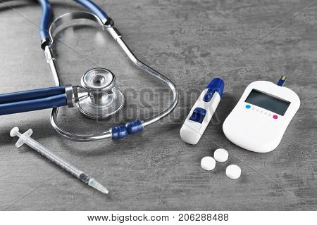 Composition with digital glucometer on grey background. Diabetes concept