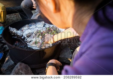 Mature Woman Grilling Food In Firepit At Forest