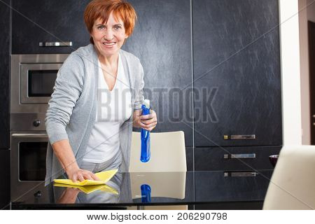 Adult woman washing glass table. Woman cleaning the kitchen.