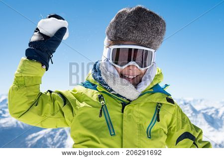 Child in yellow jacket and ski glasses playing snowballs. Happy little boy playing with snow. Child playing with snow in the snowy mountains. Child has fun during winter holiday.