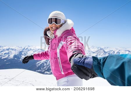 Cheerful young woman in pink winterwear holding boyfriend hand. Happy smiling couple playing and running on snowy mountain. Joyful mid woman holding hand of man during winter vacation.