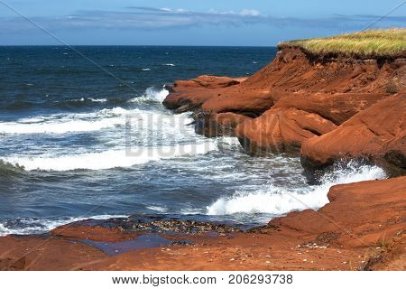 Red cliff at Cap aux Meules with waves in the ocean in the St-Lawrence golfe, iles de la madeleine in Canada