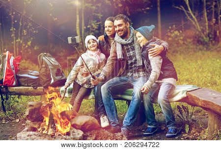 hike, travel, tourism and people concept - happy family sitting on bench and taking picture with smartphone on selfie stick at campfire in woods