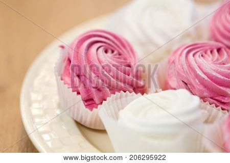 food, confection and sweets concept - close up of zephyr or marshmallow dessert on plate