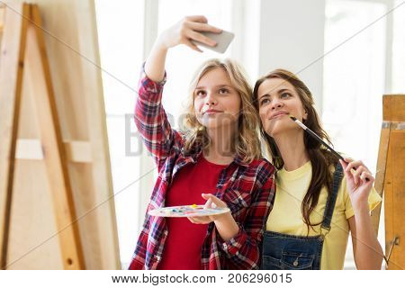 art school, technology and people concept - happy student girls or artists with smartphone, easel, palette and paint brush painting and taking selfie at studio