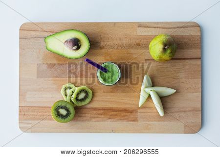 baby food, healthy eating and nutrition concept - glass jar with green fruit puree on wooden cutting board