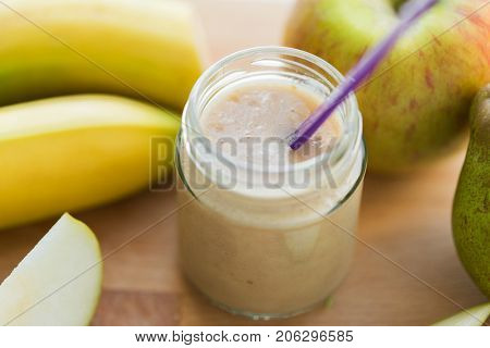 baby food, healthy eating and nutrition concept - glass jar with apple, pear and banana fruit puree on wooden board