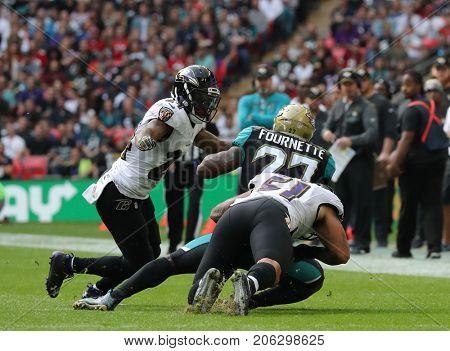LONDON, ENGLAND - SEPTEMBER 24: Kamalei Correa for Baltimore Ravens tackles Leonard Fournette for Jacksonville Jaguars during the NFL match between The Jacksonville Jaguars and The Baltimore Ravens